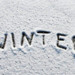 Winter written in snow on windsheild