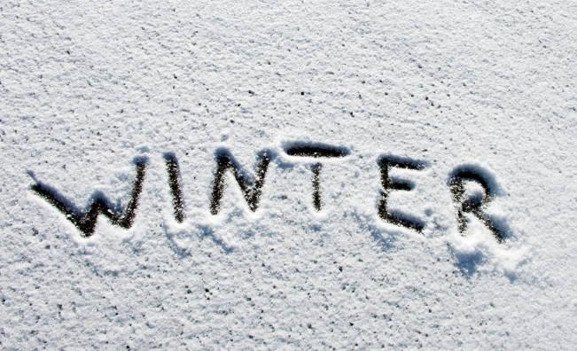 Winter written in snow on windsheild